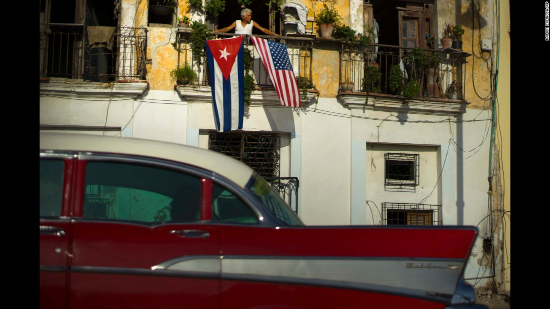 "Javier Yanez looks out from his balcony in Havana, Cuba, where he hung the national flags of Cuba and the United States on Monday, July 20. The two countries <a href=""http://www.cnn.com/2015/07/20/politics/cuba-u-s-embassies-opening/"" target=""_blank"">have re-established diplomatic relations</a> for the first time since 1961."