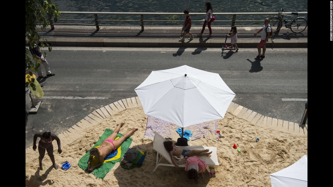 People in Paris relax on an artificial beach set up on the banks of the Seine river on Tuesday, July 21.
