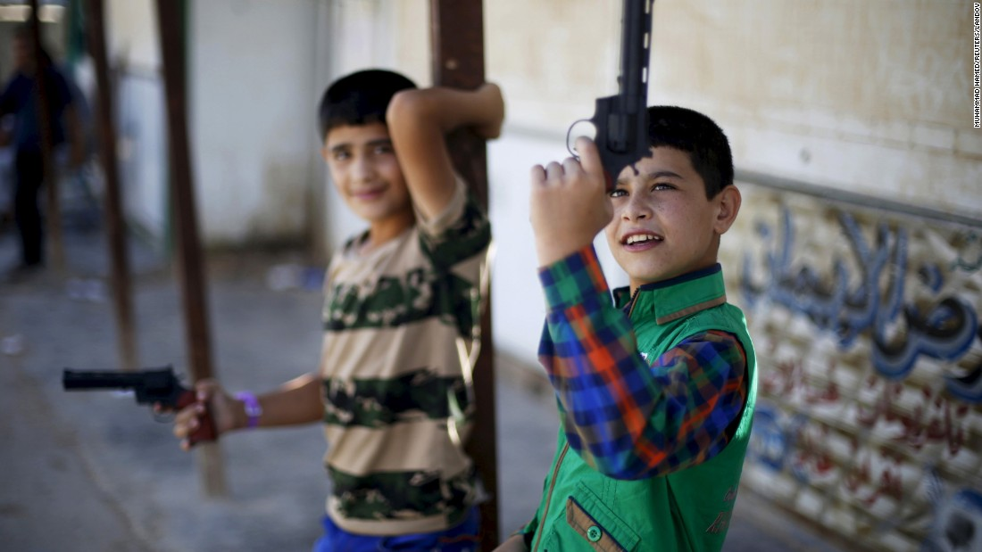 Young Syrian refugees play with toy guns at a camp in Mafraq, Jordan, on Friday, July 17. They were celebrating the first day of Eid al-Fitr, the festival marking the end of Ramadan.