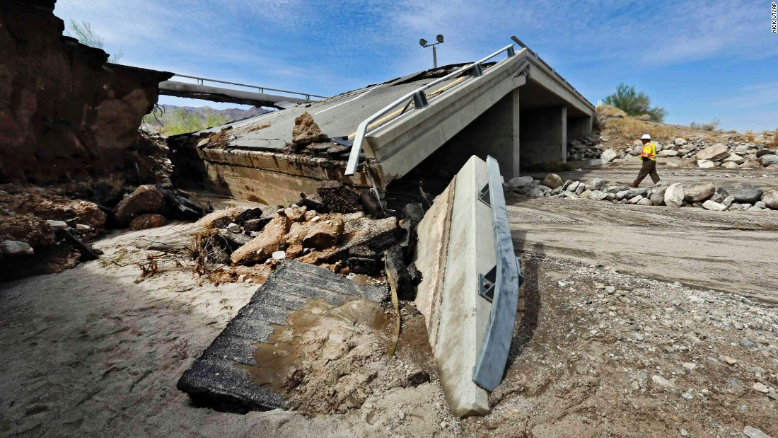A worker walks near a washed-out bridge near the town of Desert Center, California, on Monday, July 20. Traffic on Interstate 10 was blocked indefinitely when the bridge collapsed during a major storm.
