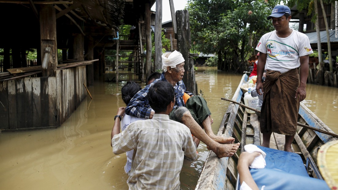 People carry an old man in a flooded village in Kawlin, Myanmar, on Tuesday, July 21.