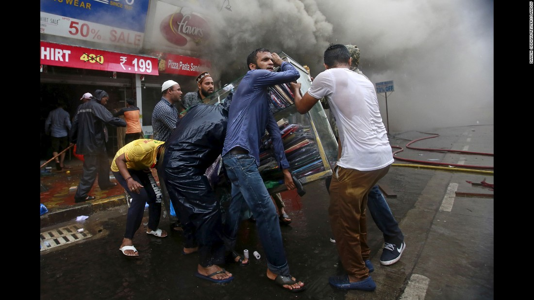 People retrieve items from a store during a fire at a shopping complex in Mumbai, India, on Tuesday, July 21.