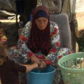 Susiya woman washing jars and bottles