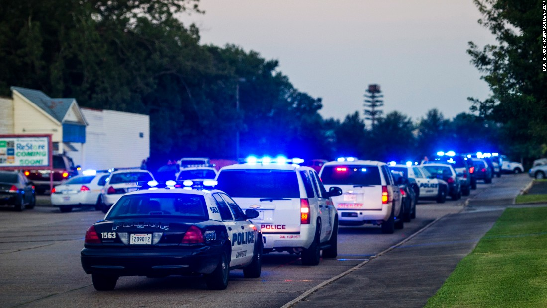 Lafayette Police Department and Louisiana State Police units block an entrance road near the scene of the shooting.