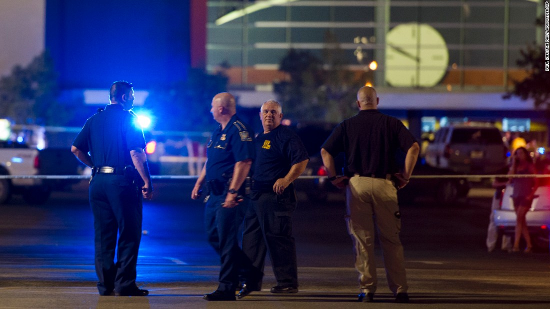 Law enforcement personnel stand near a police line at The Grand Theatre following a deadly shooting in Lafayette, Louisiana, on Thursday, July 23. The shooter in the Lafayette movie theater shooting died of a self-inflicted gunshot wound according to Louisiana State Police.