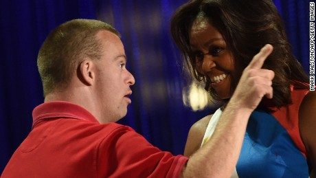First Lady Michelle Obama laughs with former Special Olympic athlete Tim Harris before she declares the 2015 Special Olympics World Games open, at the Los Angeles Memorial Coliseum on Saturday