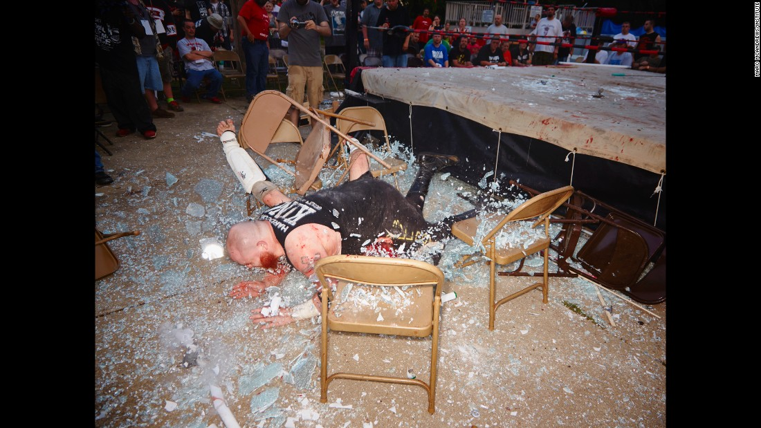 "Glass shatters as pro wrestler Matt Tremont lands on an opponent during a ""death match"" held in June 2014 by the IWA Mid-South promotion. No one, of course, actually dies in these predetermined matches, but there is plenty of blood as the performers beat each other with various weapons. ""It looks worse than it actually is. ... They know how to fall and get cut in a way that produces the most visual effect,"" photographer Marc McAndrews said."