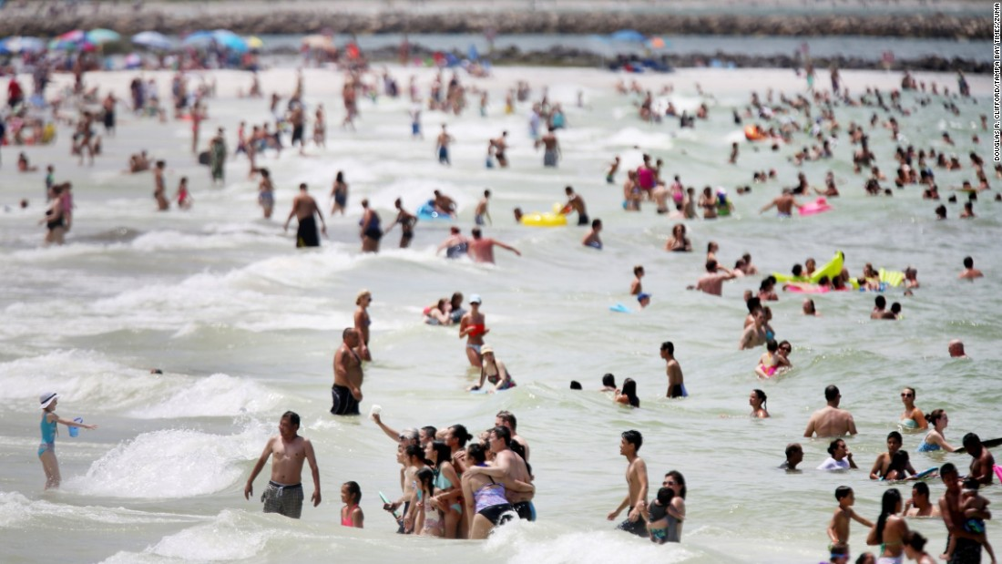 Beachgoers snap a photo together in Clearwater, Florida, on Thursday, July 23.