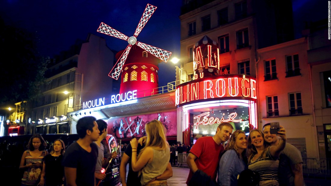 Tourists take a selfie in front of the Moulin Rouge cabaret in Paris on Friday, July 24.