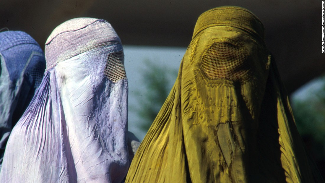 Afghan women in Kabul are covered head to toe in traditional burqas on October 16, 1996. After taking over Kabul, the ruling Taliban imposed strict Islamic laws on the Afghan people. Television, music and non-Islamic holidays were banned. Women were not allowed to attend school or work outside the home, and they were forbidden to travel alone.