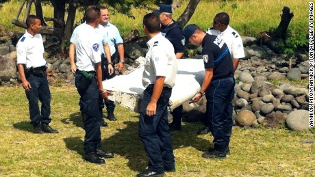 Police and gendarmes carry a piece of debris from an unidentified aircraft found in the coastal area of Saint-Andre de la Reunion, in the east of the French Indian Ocean island of La Reunion, on July 29, 2015. The two-metre-long debris, which appears to be a piece of a wing, was found by employees of an association cleaning the area and handed over to the air transport brigade of the French gendarmerie (BGTA), who have opened an investigation. An air safety expert did not exclude it could be a part of the Malaysia Airlines flight MH370, which went missing in the Indian Ocean on March 8, 2014. AFP PHOTO / YANNICK PITONYANNICK PITON/AFP/Getty Images