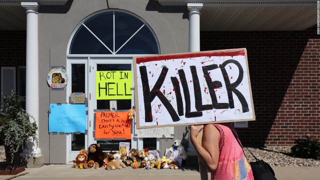 "A protester walks outside the dental practice of Walter J. Palmer, a Minnesota hunter who killed a popular lion from Zimbabwe's Hwange National Park. Palmer is in the public crosshairs after the Zimbabwe Conservation Task Force said the lion, Cecil, <a href=""http://www.cnn.com/2015/07/29/africa/zimbabwe-cecil-the-lion-killed/index.html"" target=""_blank"">was lured out of the animal sanctuary and killed.</a> Cecil was skinned and beheaded, the conservation group said, and he was wearing a GPS collar as part of research backed by Oxford University. Two Zimbabweans have been charged with poaching, and officials in the African nation say they want to talk to Palmer. ""I had no idea that the lion I took was a known, local favorite, was collared and part of a study until the end of the hunt,"" Palmer said in a statement. ""I relied on the expertise of my local professional guides to ensure a legal hunt."""