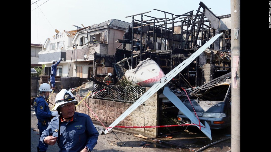 "Firefighters inspect a house that was destroyed when <a href=""http://www.cnn.com/2015/07/26/asia/tokyo-plane-crash/index.html"" target=""_blank"">a small plane crashed into a residential area</a> in Chofu, Japan, on Sunday, July 26. Three people were killed."