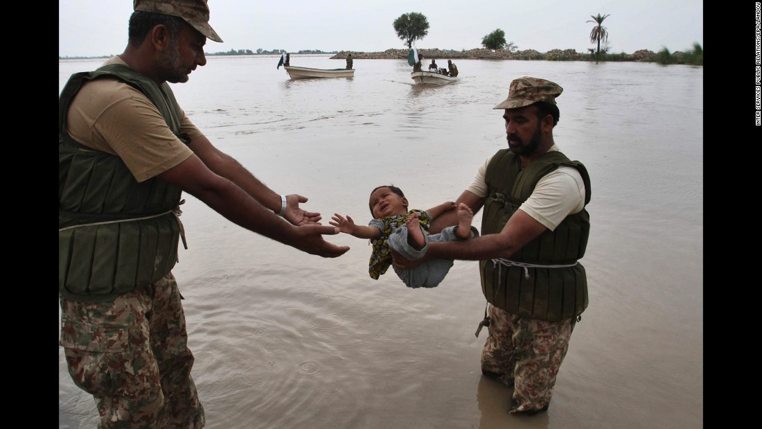 Members of the Pakistani Army rescue a young flood victim in Layyah, Pakistan, on Monday, July 27.