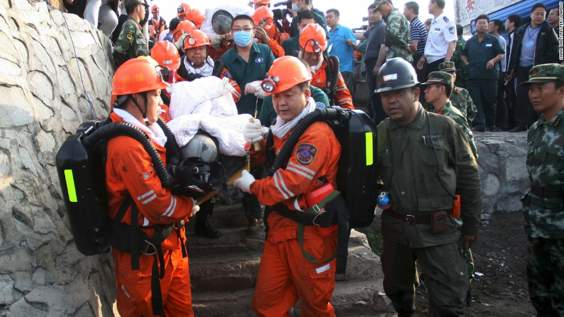 Rescuers carry miners out of a flooded coal mine in Hegang, China, on Monday, July 27. A landslide on July 20 had trapped miners underground for days. Some of the miners were rescued, but others were confirmed dead and some were still missing, according to the Xinhua News Agency.