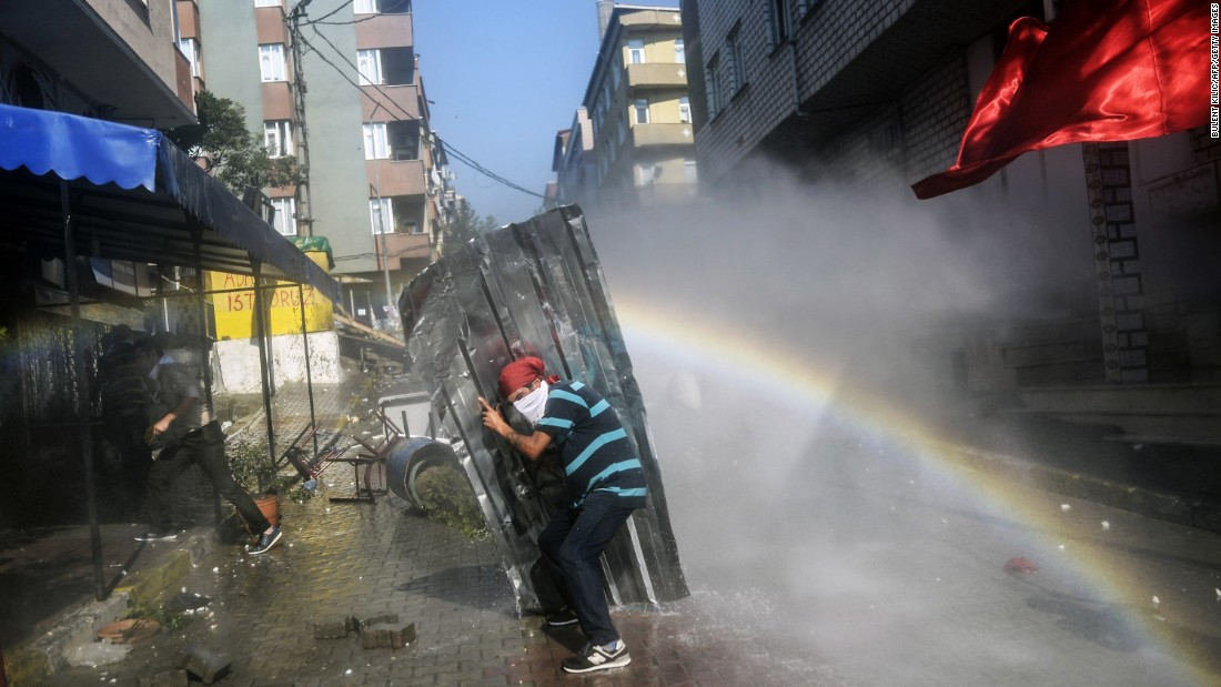 A left-wing militant shields himself from water cannons during clashes with Turkish police officers in Istanbul on Sunday, July 26.