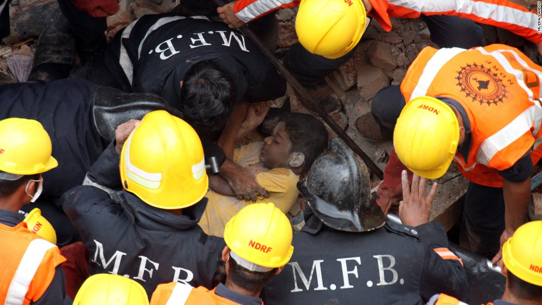 "Rescuers carry the dead body of a victim who was killed when <a href=""http://www.cnn.com/2015/07/29/asia/india-building-collapse/"" target=""_blank"">a residential building collapsed</a> in Thane, India, on Tuesday, July 28. The three-story building collapsed during heavy rain."
