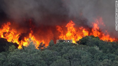 Flames from the Rocky Fire approach a house on Friday,  July 31, in Lower Lake, California.