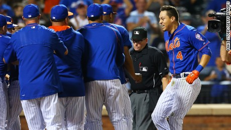 Wilmer Flores, right, of the New York Mets celebrates after hitting a home run in the 12th inning.