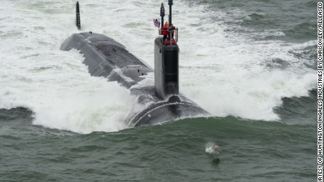 "A dolphins swims in front of Navy's newest submarine, the attack submarine USS John Warner, during its sea trials in May. The John Warner was commissioned on Saturday, August 1, in a ceremony in Norfolk, Virginia. Virginia-class attack subs, displacing 7,800 tons and at 377 feet long, ""are designed to seek and destroy enemy submarines and surface ships; project power ashore with Tomahawk cruise missiles and Special Operation Forces (SOF); carry out Intelligence, Surveillance, and Reconnaissance (ISR) missions; support battle group operations; and engage in mine warfare, according to the Navy. The Navy has 12 Virginia-class subs in service. Click through the gallery to learn more about the Navy's submarine fleet."