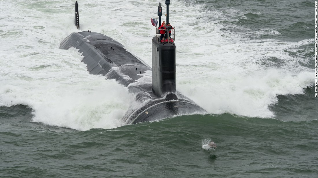 The request includes $5.2 billion to buy two Virginia-class attack submarines. Here, a dolphin swims in front of the USS John Warner during its sea trials in May.