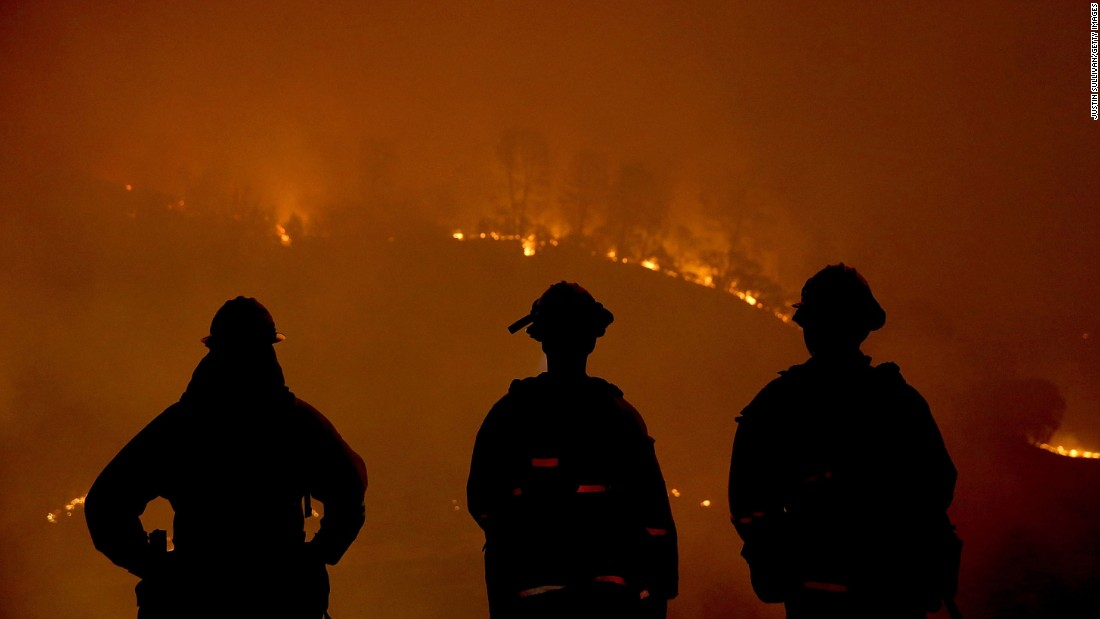 Firefighters look on as the Rocky Fire burns through trees on Sunday, August 2.