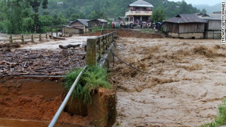 People look at the bridge which was washed away by the floodwaters in the state of Manipur, India on August 1, 2015. At least 21 people were killed in a landslide caused by heavy rains in Manipurs Chandel district, said police.