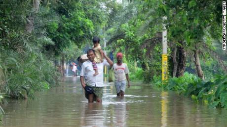 Indian villagers wade through floodwaters in Bherampur Block, Murshidabad. In Gujarat, India's westernmost state, 71 people have died, 69 people have died in West Bengal and 38 have died in Rajasthan according to the State Home Ministry Spokesman Kuldeep Dhatwalia.