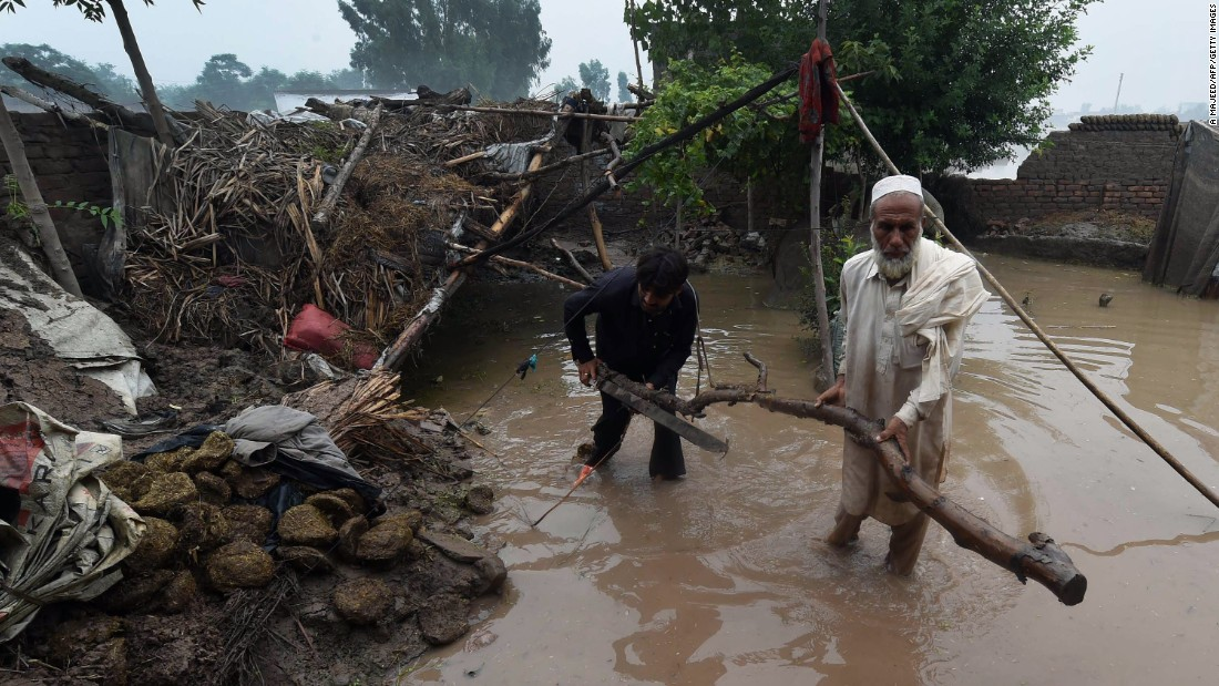 Pakistani men clear up next to a partially damaged house in the Khyber Pakhtunkhwa province on August 3, 2015. A spokesman for Pakistan's National Disaster Management Agency told AFP that 116 people had died and more than 850,000 people had been affected across the country by this year's monsoon floods.