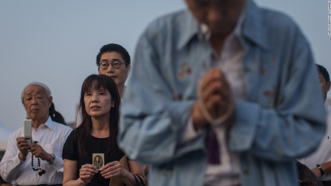 A woman holds a photograph as she prays at the Hiroshima Peace Memorial on August 6.