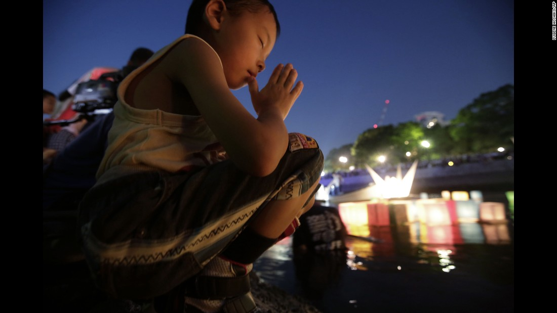 A boy offers prayer as after releasing a paper lantern into the Motoyasu River on August 6.