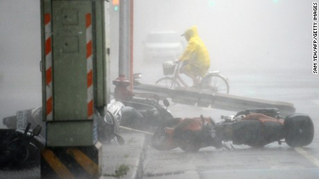 A man rides past blown down motorcycles as typhoon Soudelor hits Taipei on August 8, 2015. Typhoon Soudelor battered Taiwan with fierce winds and rain leaving four people dead and a trail of debris in its wake as it takes aim at mainland China. AFP PHOTO / Sam YehSAM YEH/AFP/Getty Images