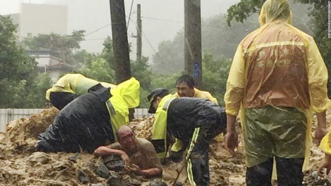 Emergency rescue personnel dig a man from a mudslide caused by Typhoon Soudelor in Xindian, New Taipei City, Taiwan, on Saturday, August 8.