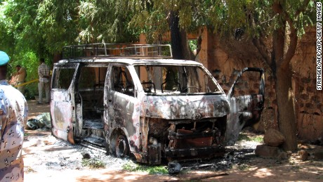 A burned vehicle sits in front of the Hotel Byblos in the Sevare, Mali, after gunmen stormed the hotel on Friday, August 7.