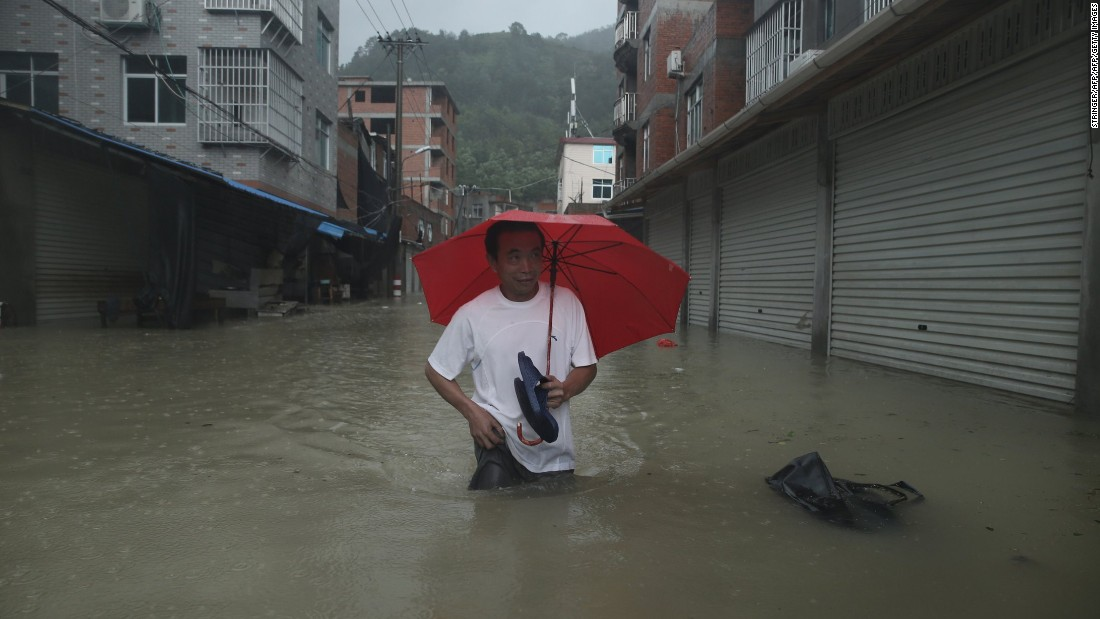 A man wades through a flooded street in Ningde, China, on Sunday, August 9. Soudelor made landfall Saturday night in the city of Putian, in China's southern Fujian province. More than 185,000 people moved to higher ground, Xinhua reported. The typhoon weakened as it moved inland toward the northwest.