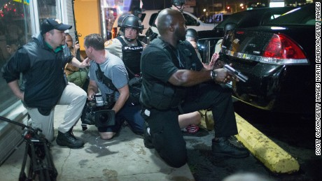 Police take cover as a barrage of gunfire erupts during a demonstration to mark the one-year anniversary of the shooting of Michael Brown on August 9, 2015, in Ferguson, Missouri.