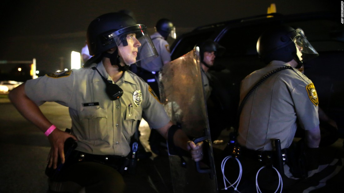 Police take cover after gunfire in Ferguson on August 9.