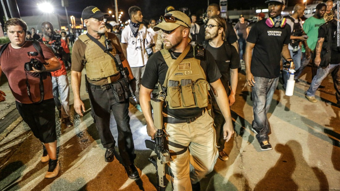 "Members of a group calling themselves the ""Oath Keepers"" appear in Ferguson carrying large guns on Monday, August 10, one day after a police confrontation led to a protester being shot. Sunday, August 9, marked the one-year anniversary of the death of Michael Brown."