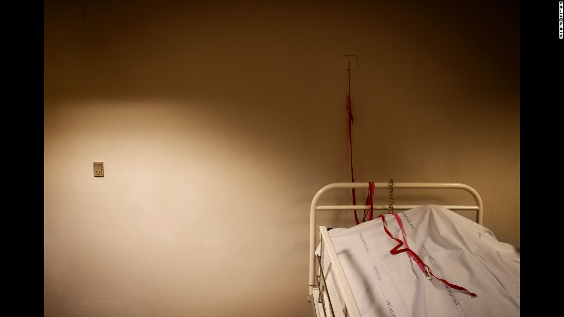 "In the ""Sixhour Room"" lies a man under a blanket. Ertmann said that before six hours have passed from the moment of his death, a doctor will examine the body, looking for signs of clinical death such as bruising and stiffness. The red cord seen in this photo has never been used in the chapel in Aarhus, but it's<br />there anyway, so that the person under the cloth can call for help should they awaken."