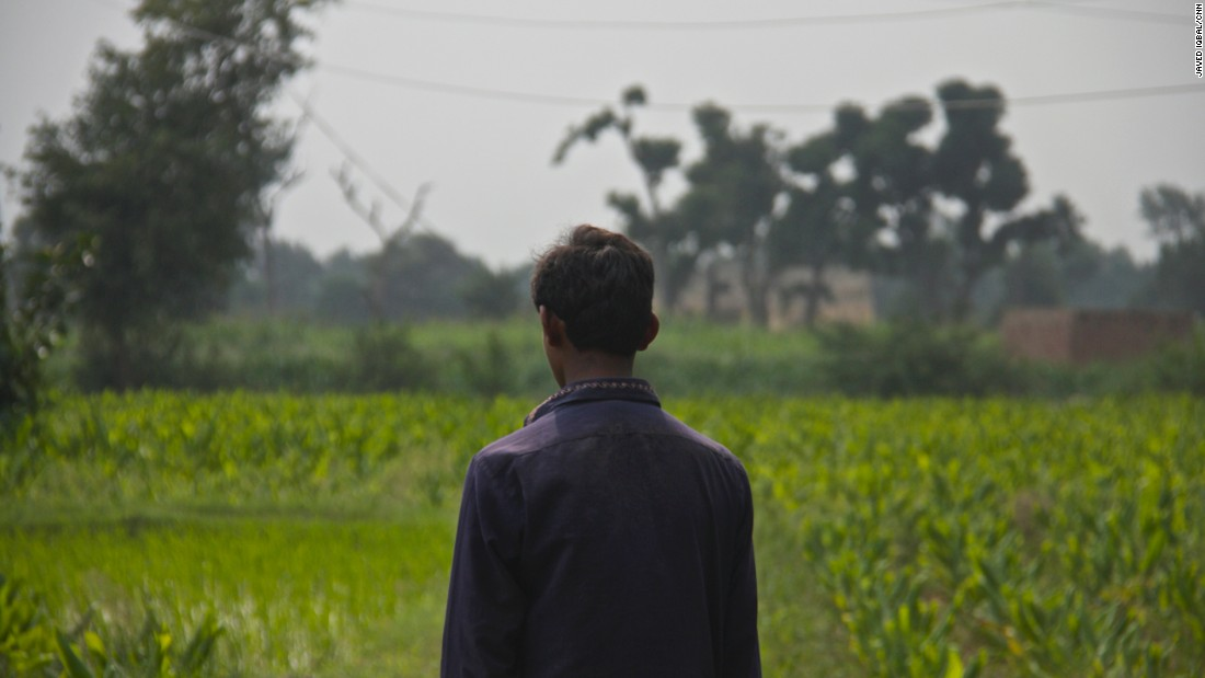 A boy who says he was molested and filmed looks across a field where he says many children, including him, were abused and raped in a story that has shocked Pakistan.