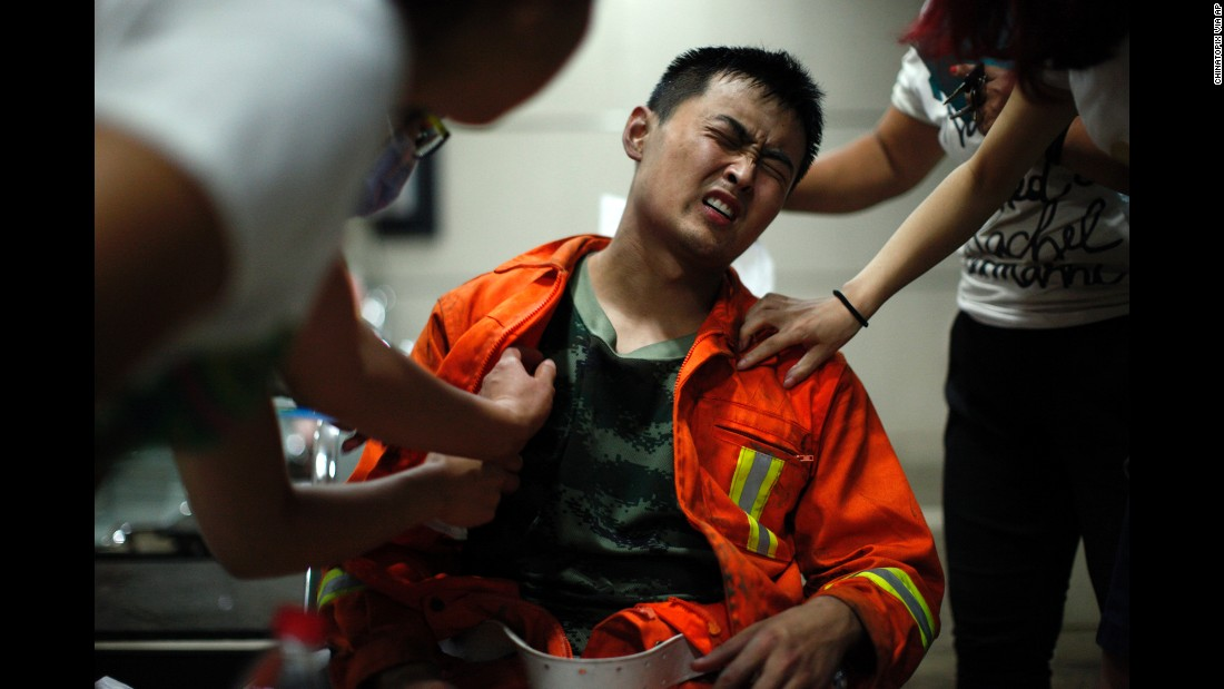 A firefighter grimaces as he is examined for injuries. Seventeen firefighters were among the people killed, officials said.