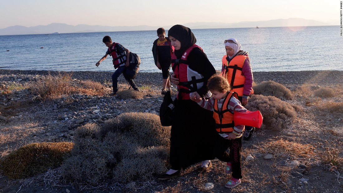 A Syrian migrant mother holds the hand of a child as they arrive at a beach on Kos on August 13.