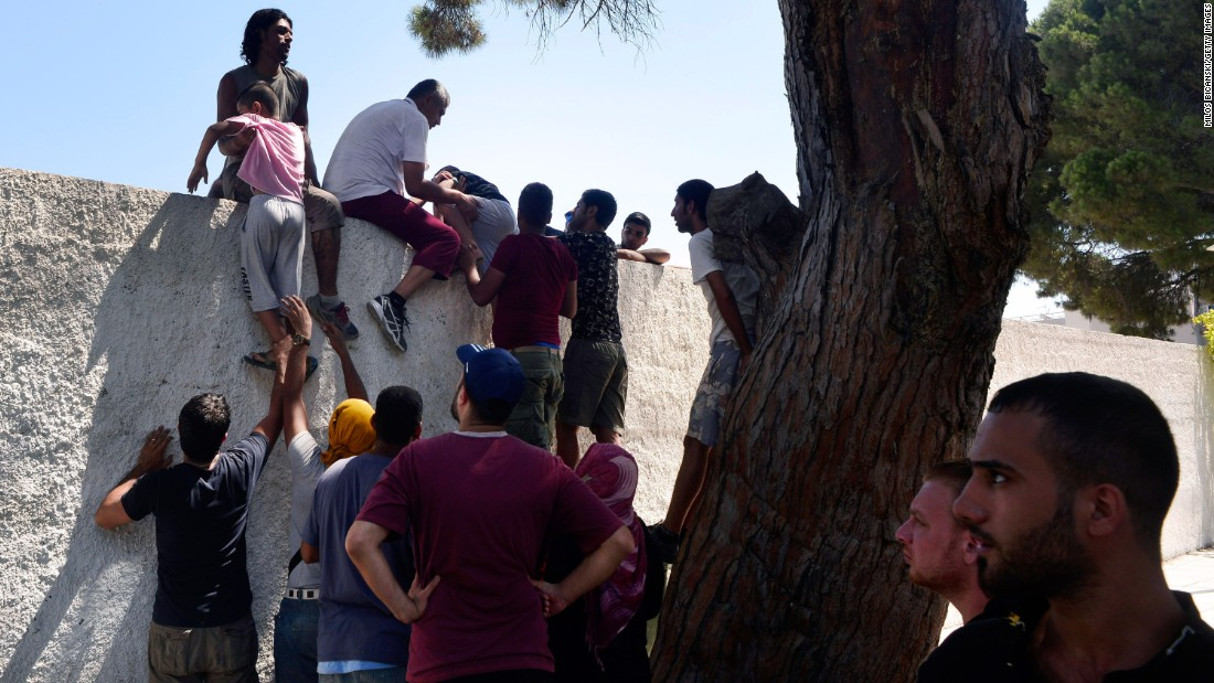 Migrants climb a wall of the national stadium where registration for the migrants was taking place on August 12.