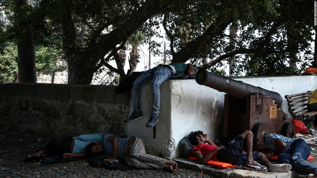 Migrants sleep in a central square of Kos on August 10.