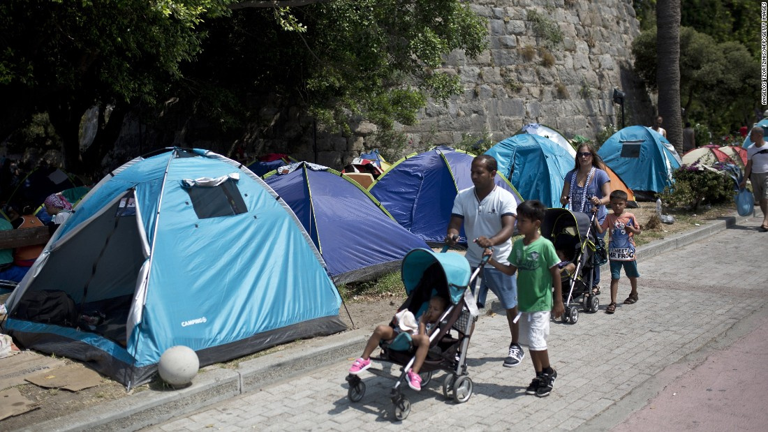 People walk past tents of migrants set up in the street on August 10.