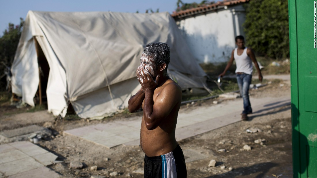 A migrant washes his face near a deserted hotel, where hundreds of migrants have found temporary shelter, on August 10.