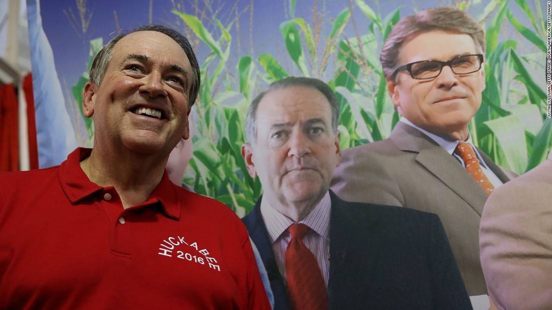Former Arkansas Gov. Mike Huckabee stands next to a poster featuring all of the Republican candidates as he tours the fair on August 13.