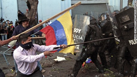 Riot policemen clash with demonstrators in Quito, Ecuador on August 13, 2015, during a strike organized by opposition indigenous groups and unions. Demonstrators took to the streets around Ecuador on Thursday to protest President Rafael Correa's moves to seek a fourth term, but the leftist leader declared that plans for a paralyzing general strike had failed.