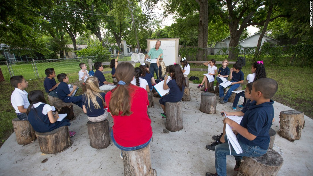 An educator with the REAL School Gardens program talks with students in their outdoor classroom at Burton Hill.