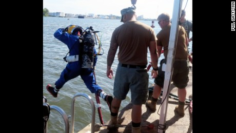A U.S. Navy diver, after a briefing and gear check, strides into the turbid Savannah River.